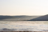 Evening landscape: mountains in the sunset haze, a wide river and a village at the foot of the mountains on the opposite shore. Zhiguli Mountains, Volga River, Samara Region - 227819609