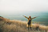 Cheering woman enjoy the beautiful view at mountain peak - 227826020