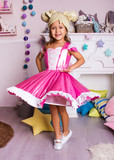 little girl in pink ballerina dress. kid christmas halloween costume. young girl dancer in white room is standing and dancing in pink fancy skirt and hat like hair
