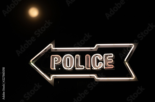 White Neon Sign Points Towards Police Station Dark Night Full Moon