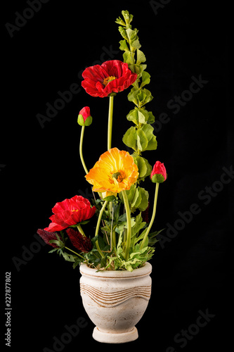Floral arrangement from artificial poppy flowers in old ceramic flower pot. - 227877802