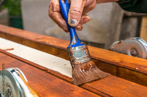 Painter with paintbrush painting wooden surface - 227878278