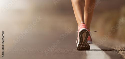 Leinwanddruck Bild Running shoe closeup of woman running on road with sports shoes