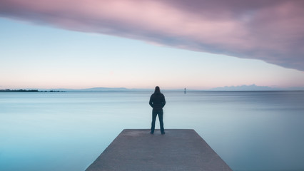 Silhouette of man sitting on pier at dawn © Paul McConville