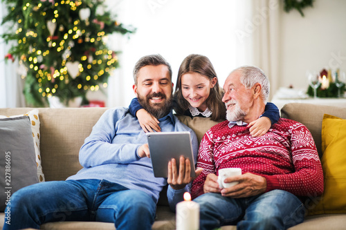 Leinwandbild Motiv Small girl and her father and grandfather sitting on a sofa at Christmas, using tablet.
