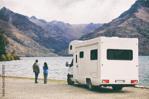RV motorhome camper van road trip young people on New Zealand travel vacation adventure, Two tourists looking at lake and mountains on pit stop next to their rental car.