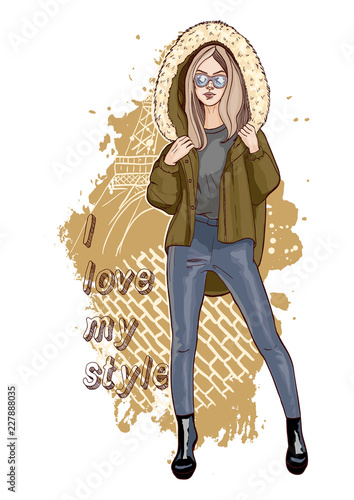 Beautiful young woman in stylish clothes. Casual style. Fashion model posing. Vector illustration with slogan. Girl is wearing a hooded jacket. Hand drawn sketch.