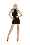 young pretty blonde woman posing in short black dress on white background