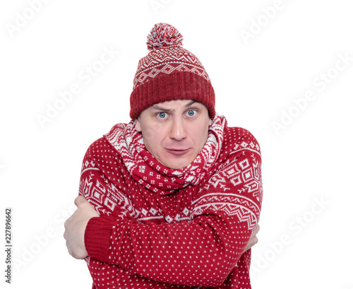 Foto Murales Frozen man in red sweater, scarf and hat warming hands, isolated on white background. File contains a path to isolation.