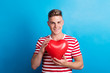 Leinwandbild Motiv A young man in a studio, holding red heart balloon in front of him.