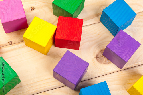 colorful wooden cubes on wooden table © NewFabrika