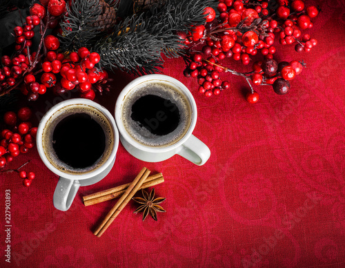 Wall mural Cups of fragrant coffee on a Christmas background of fir branches, berries and cones