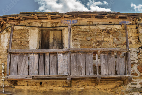 Foto Murales Old vintage run-down wooden balcony, stone facade