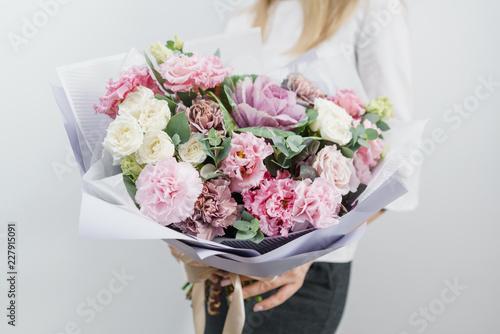 piękny bukiet wiosenny. Młoda dziewczyna trzyma kwiaty uzgodnień z różnych kolorów. Biała ściana.