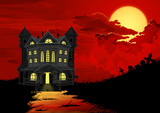 Halloween background. Haunted house with lighted windows, on right side silhouette of graveyard. On the sky big full moon behind blood red clouds.
