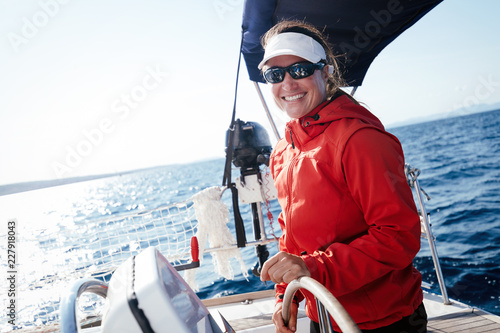 Attractive strong woman sailing with her boat - 227918043