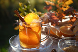 hot tea drink with orange slices and cinnamon in a glass cup in backlit in the autumn garden, selected focus, narrow depth of field - 227918495