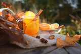 hot tea with orange slices and cinnamon on a wooden garden table with a blanket and autumn leaves, copy space - 227919434