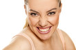 frowned and happy woman shows her teeth on a white background