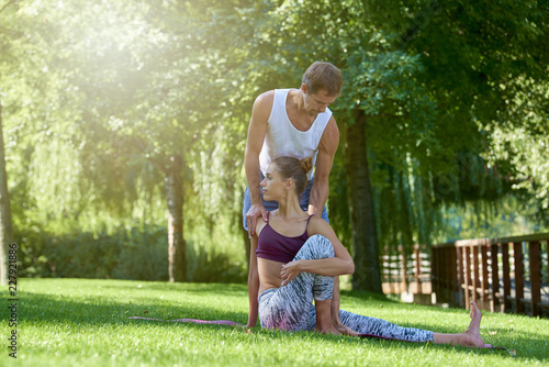 Fototapeta Young woman and her yoga insructor practicing yoga outdoor