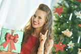 woman with green Christmas present box with raised fingers drawing attention