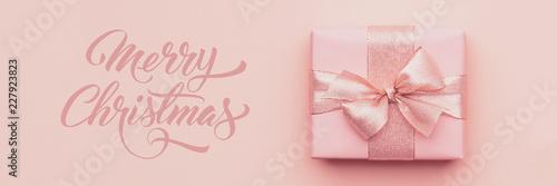 Transparent świąteczny. Piękny różowy prezent na Boże Narodzenie na pastelowych różowym tle papieru.