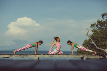 three asian woman playing yoga flow on beach pier