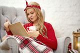 young beautiful woman sitting and reading a book and drinking tea in an armchair wrapped in a blanket during Christmas time - 227932825
