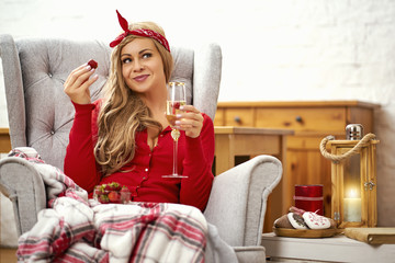 young smiling beautiful woman in an armchair with a glass of prosecco wrapped in a blanket during Christmas time