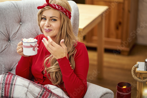 młoda uśmiechnięta piękna kobieta w fotelu z filiżanką gorącej czekolady zawinięte w koc podczas świąt Bożego Narodzenia