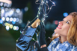 Young woman holding christmas fairy lights at night outdoors in city - 227943432