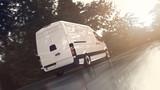 Weißer Transporter fährt schnell auf einer nassen Landstraße der Sonne entgegen - 227943447