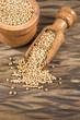 Yellow mustard grains - Sinapis alba. Wooden background