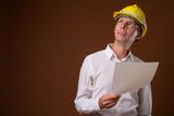 Portrait of businessman wearing hardhat against brown background - 227949463