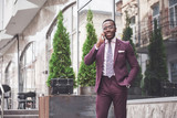 Portrait of a young and handsome African American businessman talking in a suit over the phone. Preparing for a business meeting. - 227952895