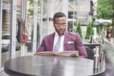 A beautiful African American businessman reads a menu in a cafe - 227953020