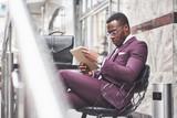 A beautiful African American businessman reads a menu in a cafe - 227953079