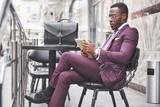 A beautiful African American businessman reads a menu in a cafe - 227953096