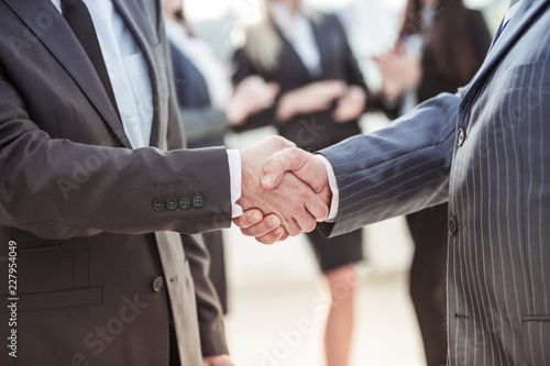 Fridge magnet concept of cooperation - handshake of business partners on the background of the employees in the office