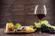 Leinwanddruck Bild - wine glass and bunch of grapes on wooden table