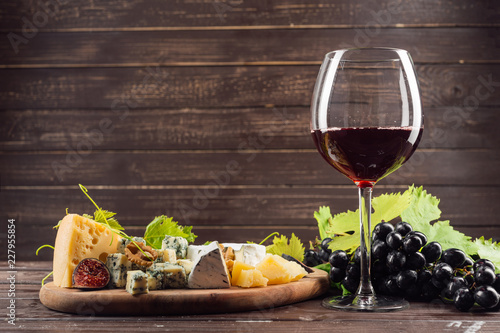 Leinwanddruck Bild wine glass and bunch of grapes on wooden table