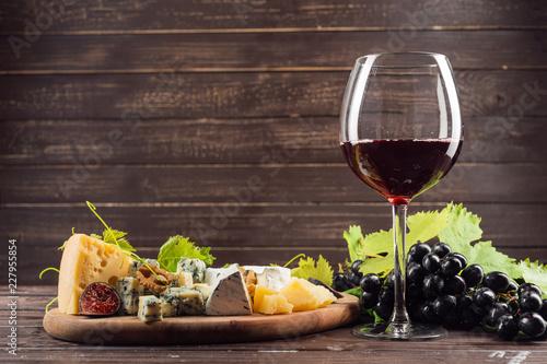 Leinwandbild Motiv wine glass and bunch of grapes on wooden table
