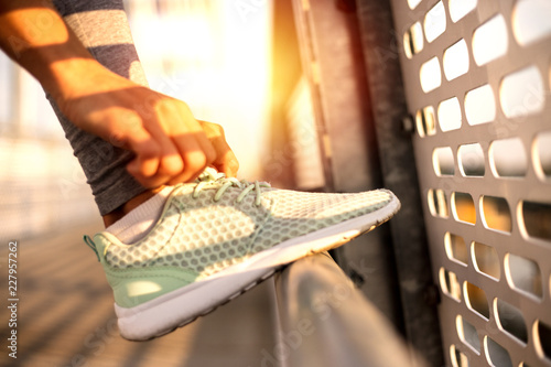 Fototapeta fit woman tying the laces on her running shoes while standing on a bridge