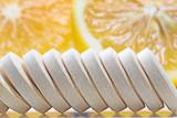 Row of  Vitamin c tablets and fresh lemon - 227972081