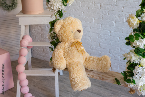 The toy teddy bear sits on the nursery a swing