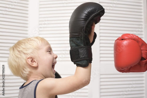 Blond boy boxing with hand in red glove. Emotions