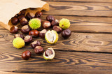 Whole and broken green prickly chestnuts and smooth brown chestnuts poured out of paper package on old wooden rustic brown table with copy space for your text - 227983416
