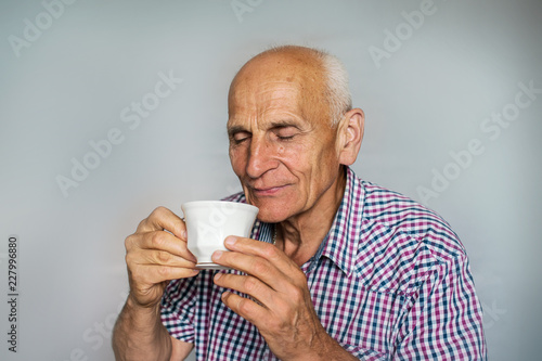 Foto Murales An elderly man with a cup of tea or coffee in his hands inhales the fragrance