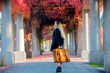 Young girl with suitcase in red grapes alley. Autumn season time