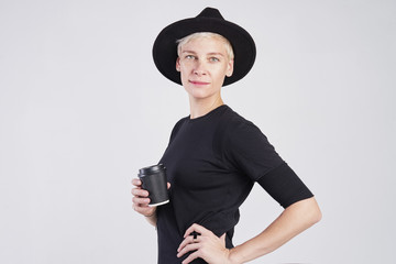 Portrait of blond caucasian woman wearing black clothes and hat having disposable paper cup of coffee, posing on white background. © olgapogorelova